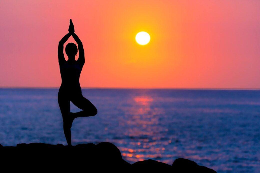kvinde laver yoga i solnedgang
